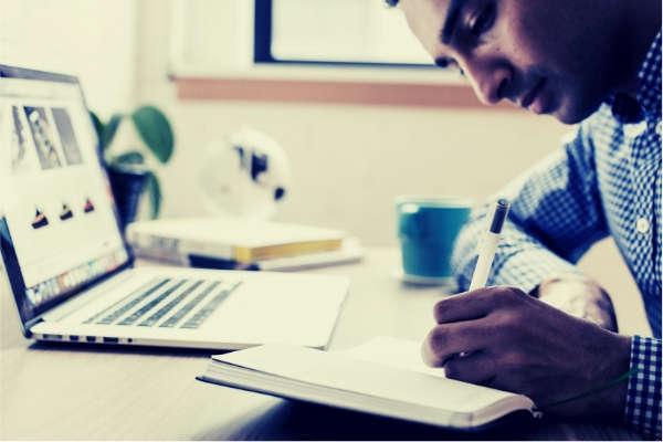 08-man-using-ballpoint-pen-writing-notebook-laptop-bokeh-shot