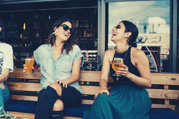 12-feature-two-smiling-women-sitting-on-wooden-bench