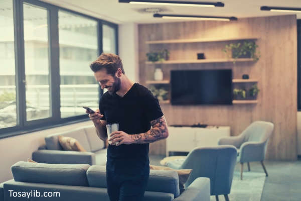 man-in-black-shirt-standing-while-holding-drinking-glass-texting-smiling