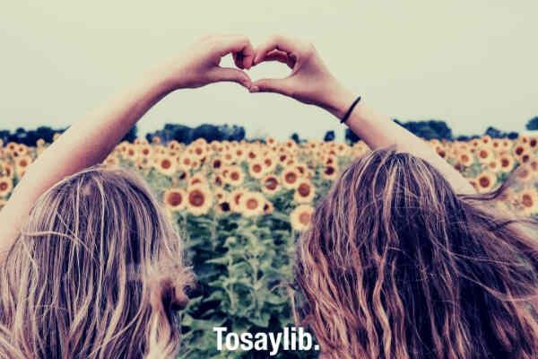 two friends making heart using hands sunflower farm