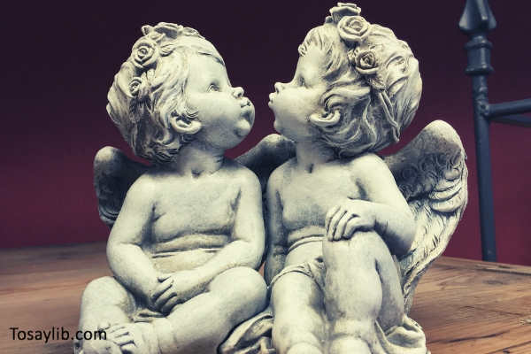 angels sculpture statue cherub staring up red wall