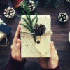 35-feature-brown-pinecone-on-white-rectangular-board-person-holding-gift