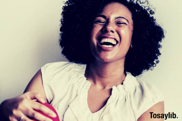 woman wearing white sleeveless top and red bottoms laughing