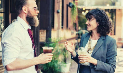 feature-man-woman-talking-wearing-office-outfit-holding-beverages