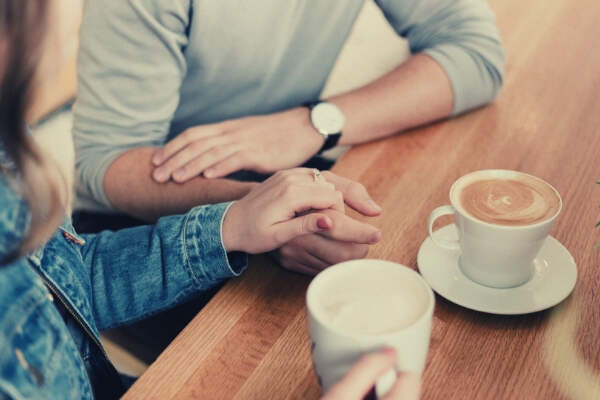 11-feature-couple-holding-hands-while-drinking-coffee