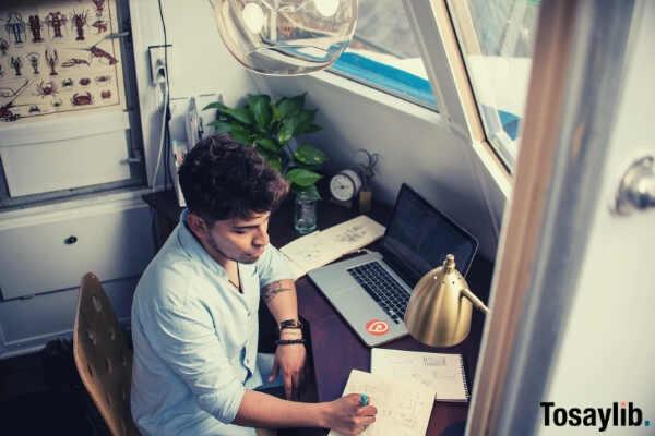 man working laptop beside window