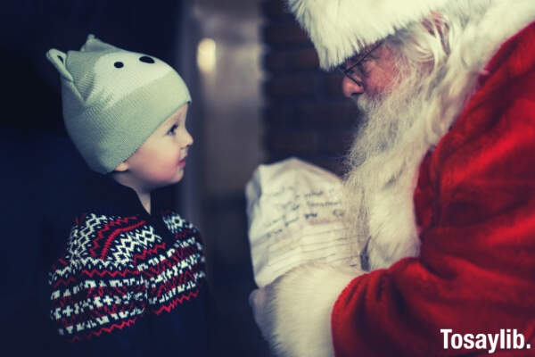 santa claus giving gift to a little boy