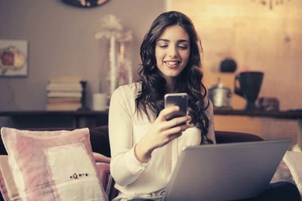 23-feature-woman-sitting-on-sofa-while-looking-at-phone-with-laptop-on-lap