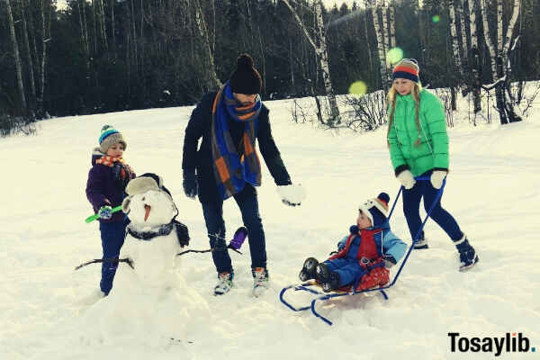 four persons playing on snow