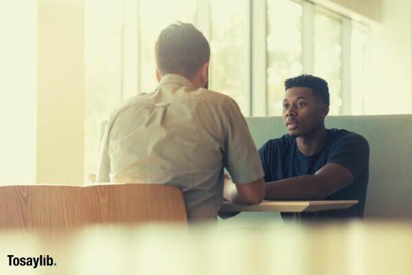 01 two men talking sitting black american
