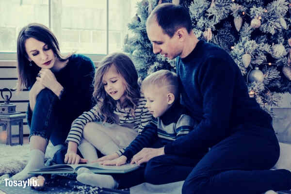 08 family sitting beside christmas tree reading book