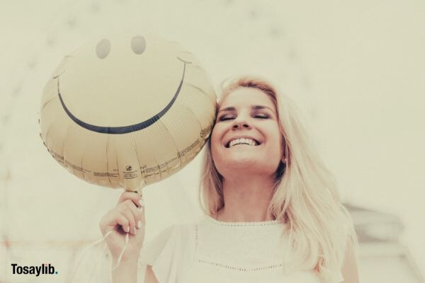 woman holding a smiley balloon