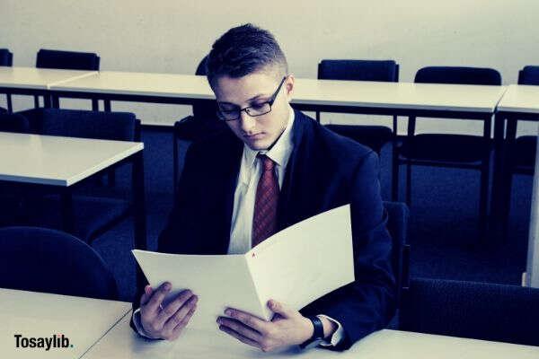 man in black suit reading