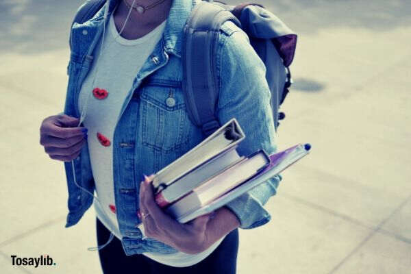 woman carrying books wearing denim jacket