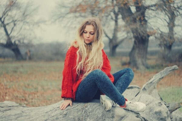 Feature-woman-in-red-sweater-sitting-on-cutted-tree