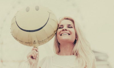 feature-woman-holding-a-smiley-balloon