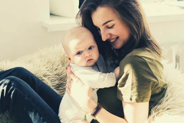 feature-woman-in-green-shirt-holding-baby-while-sitting