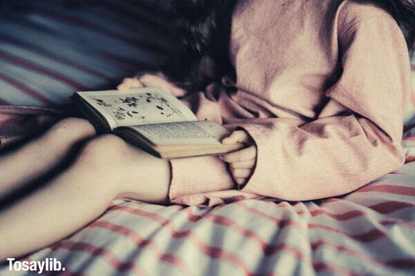 girl wearing pink dress sitting on bed reading book