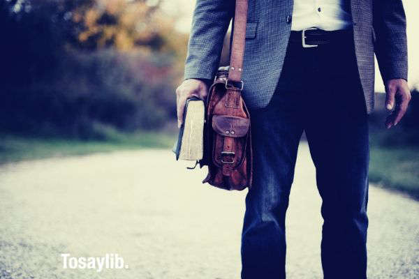 man wearing suit leather bag holding book v2