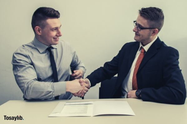 two men shaking hands formal smiling