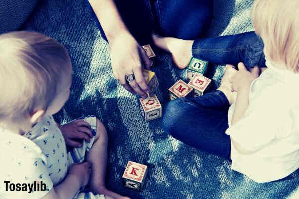 person teaching two kids letters blocks