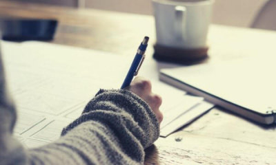 21-feature-person-holding-ballpen-writing-on-paper
