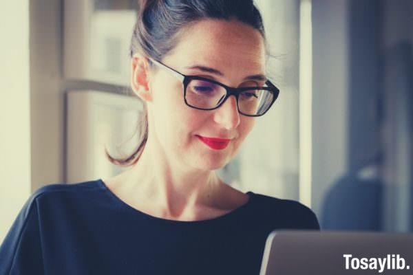 woman in black wearing black eyeglass looking at the screen 1