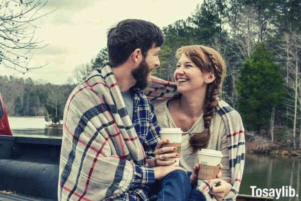 couple holding coffee covered with blanket sitting back truck