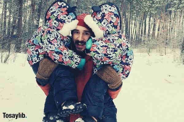 happy father and children twins cuddle snow forest
