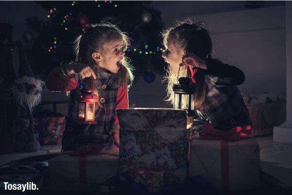 christmas night two girls open the gifts under the tree new years stories real emotions