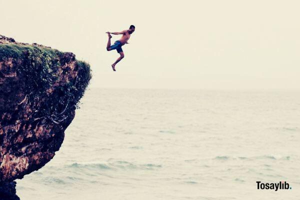 man jumping on cliff ocean
