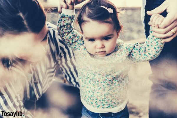 little girl wearing long sleeves two adults with her