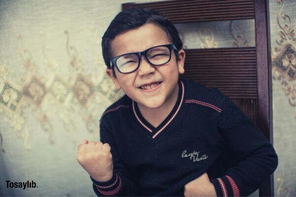 kid wearing black sweater eye glass fist