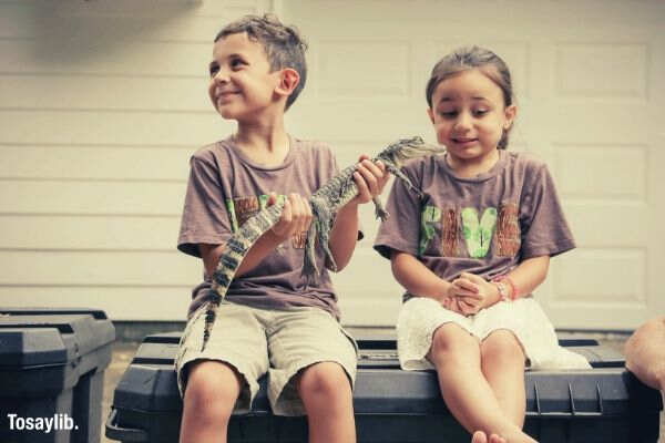 boy holding a baby alligator girl scared