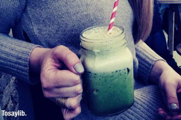 girl in sweater drinking green juice