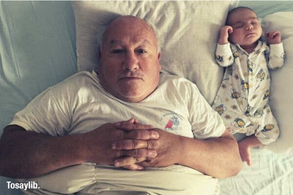 grandfather and baby sleeping lying at home