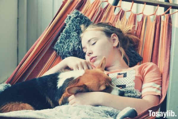 girl and her dog sleeping in the hammock