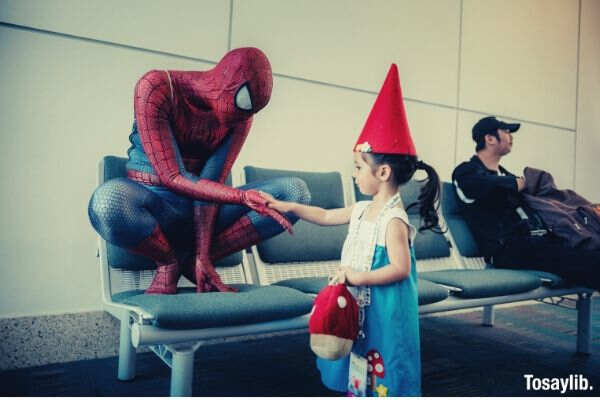 spiderman kid wearing red hat holding hand