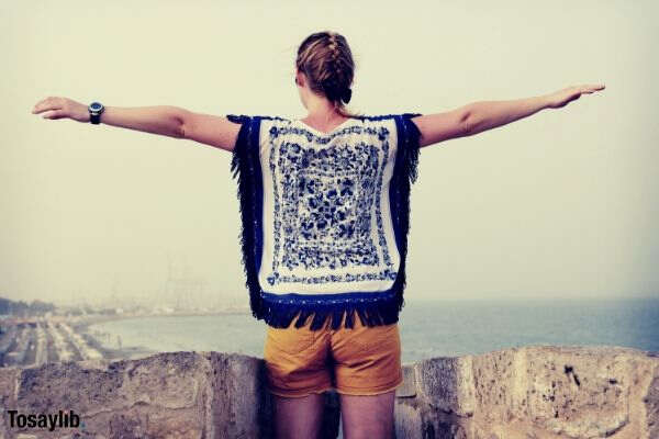 woman with blonde braided hair looking at the sea hands wide spread from up a stone wall
