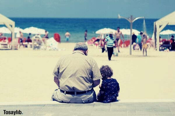 grandpa and little boy sitting on a long beach bench