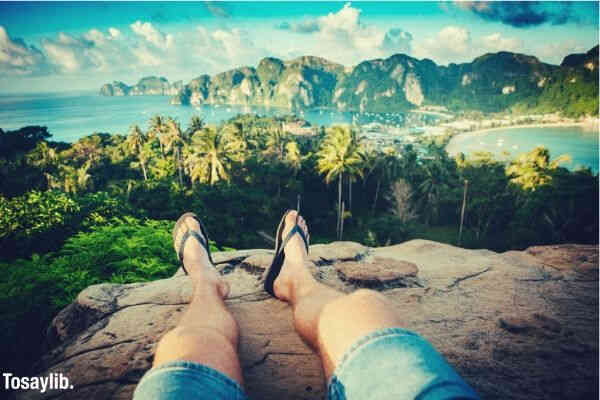 legs cliff view beach tress mountains