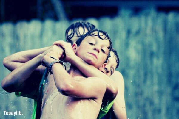 boys holding water hose