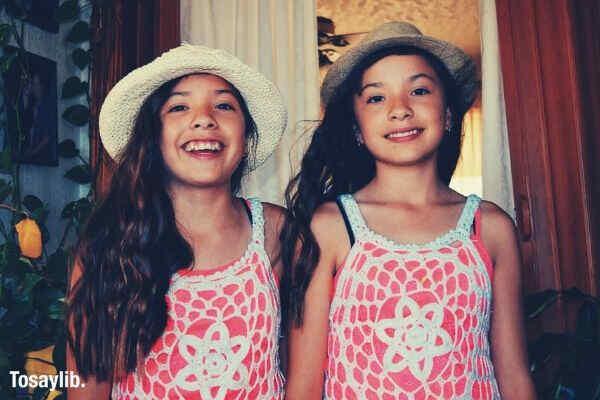 two girls wearing white pink top hat