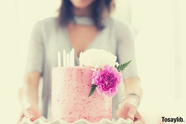 woman holding pink cake with flower