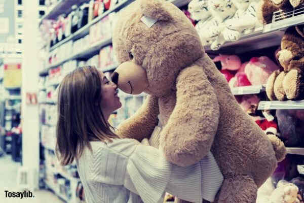 woman carrying bear plush toy inside store