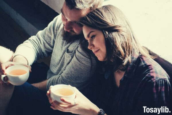 couple holding tea sitting