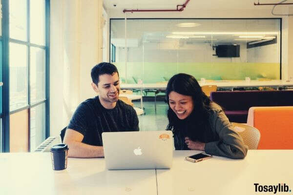 man woman looking on laptop working coffee office