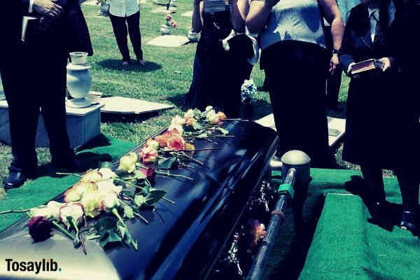 flowers on top of coffin mourning people wearing black