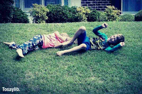 twins rolling down a hill in their front yard