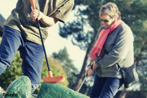 boy playing mini golf with his grandma about to get the ball into the hole